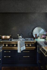 Backsplash och fläktkåpa inklädd i belgisk kalksten och spis med detaljer i mässing