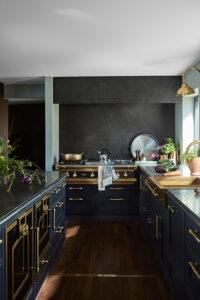 Detaljer i mässing bryter av och accentuerar det mörkt blå köket