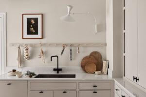 Kök, vägg och knopplist målade ton i ton med kran och knoppar som bryter av i svart